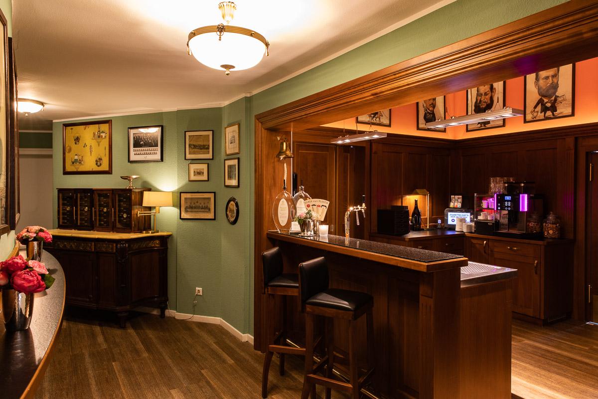 Die gemütliche Bar mit grünen Wänden und viel dunklem Holz