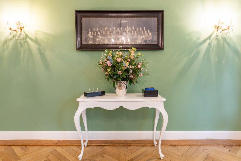 weisses Sideboard in der Veranda mit silberner Vase und üppigem Blumenstrauss