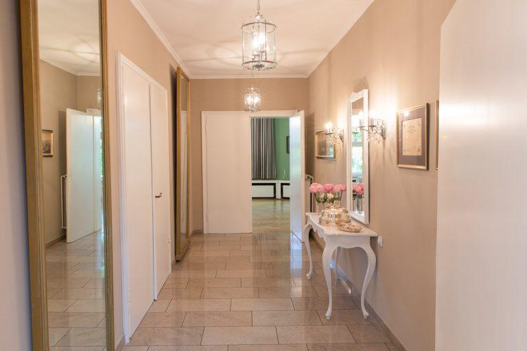 Verbindungsflur mit beigen Wänden Spiegeln und Sideboard zwischen Veranda und Eingang