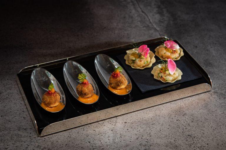 Vorspeise auf silber Löffeln und kleinen Tartlets mit essbaren Blüten