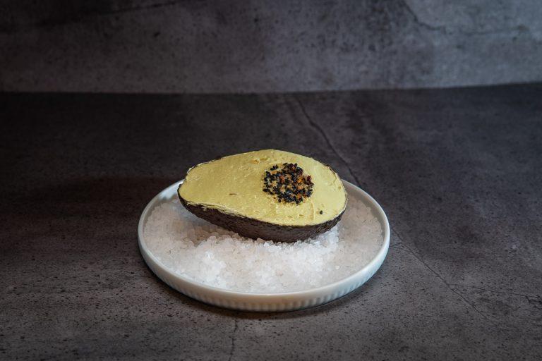 Advocadobutter pränsentiert in der Advocadoschale mit Pfeffer als Kern dekoriert und auf Salzbett angerichtet