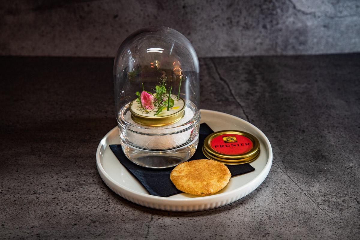Caviarshot von Prunier mit Creme fraiche Haube und Kräutern unter einer Glasglocke mit Blini