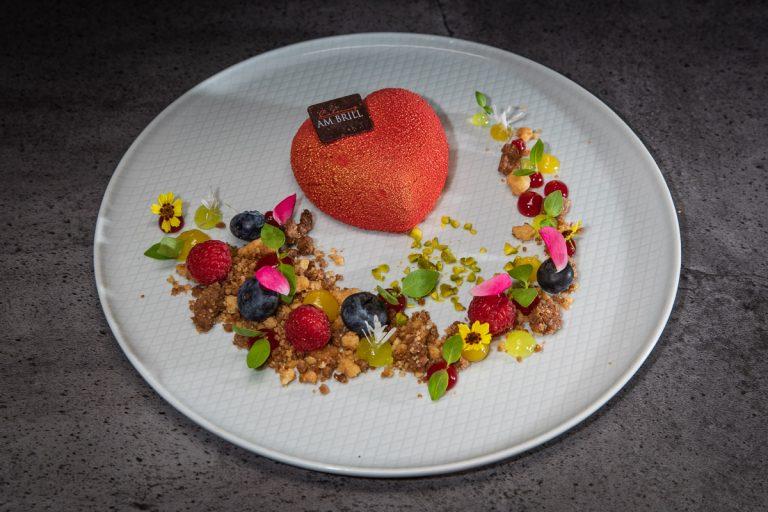 Dessertteller mit Himbeermousseherz und Beerenvariationen auf Nusscrumble
