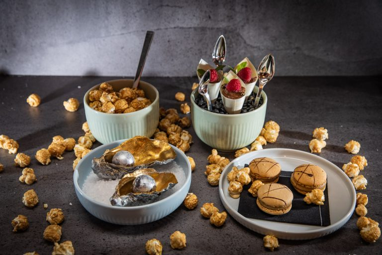 Dessertvariationen mit Popcorn, silbern lackierten Pralinen in Austernschalen und kleine Tütchen mit Schokomousse und Himbeeren