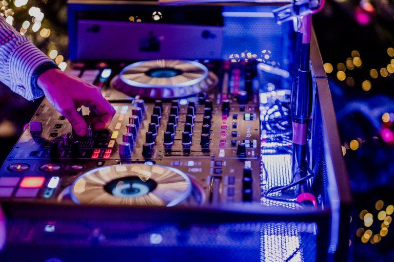 DJ Pult in Aktion mit Reglern in stimmungsvollem Licht