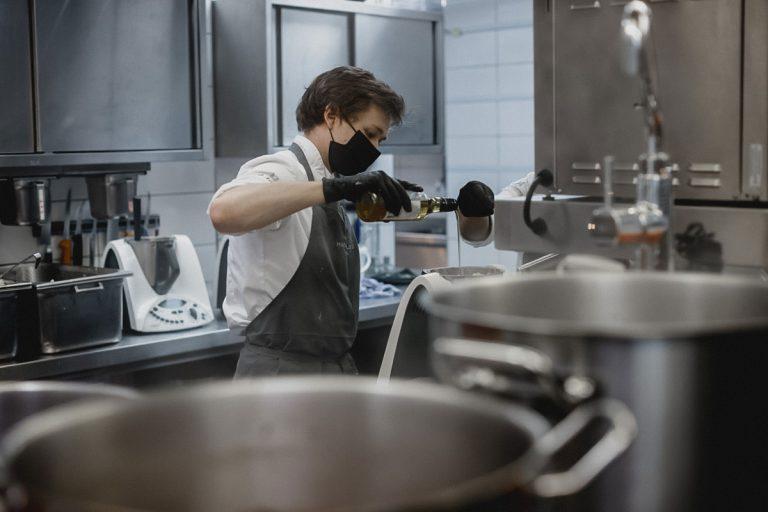 Auszubildender Koch bei der Arbeit in der modernen Küche von 1805