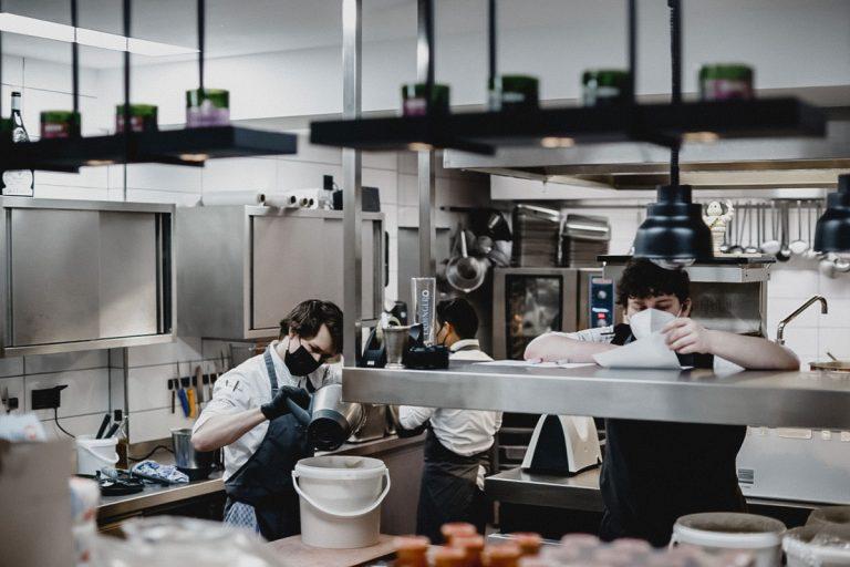 Auszubildende Köche bei der Arbeit in der modernen Küche von 1805