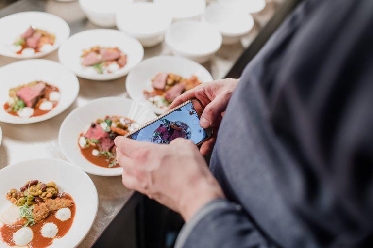 Gast der Küchenparty macht ein Handyfoto von Speisen am Pass in der Küche