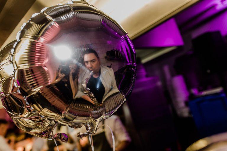 Saxophonspieler spiegelt sich in einem Ballon bei der Küchenparty