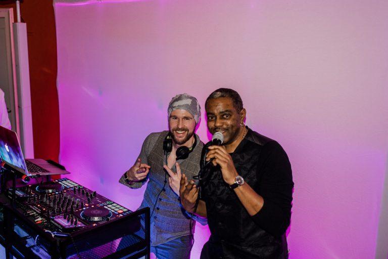 DJ Jerome mit Sänger in Aktion am Mischpult bei einer Küchenparty