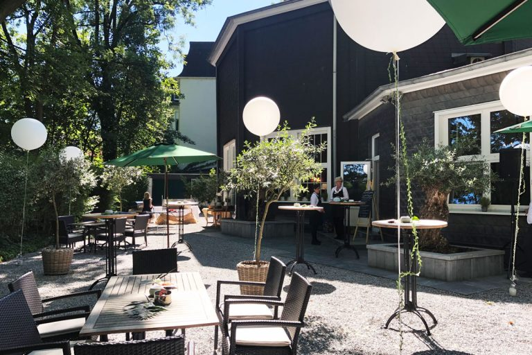 Das Bild zeigt den Garten mit Tischen und großen weißen Ballons