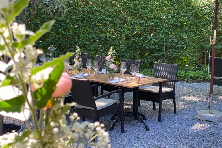 Das Bild zeigt gedeckte Tische im schönen Garten