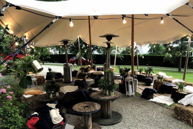 lougcatering unter einem großen Schirm mit Strohballen und Holzstämmen