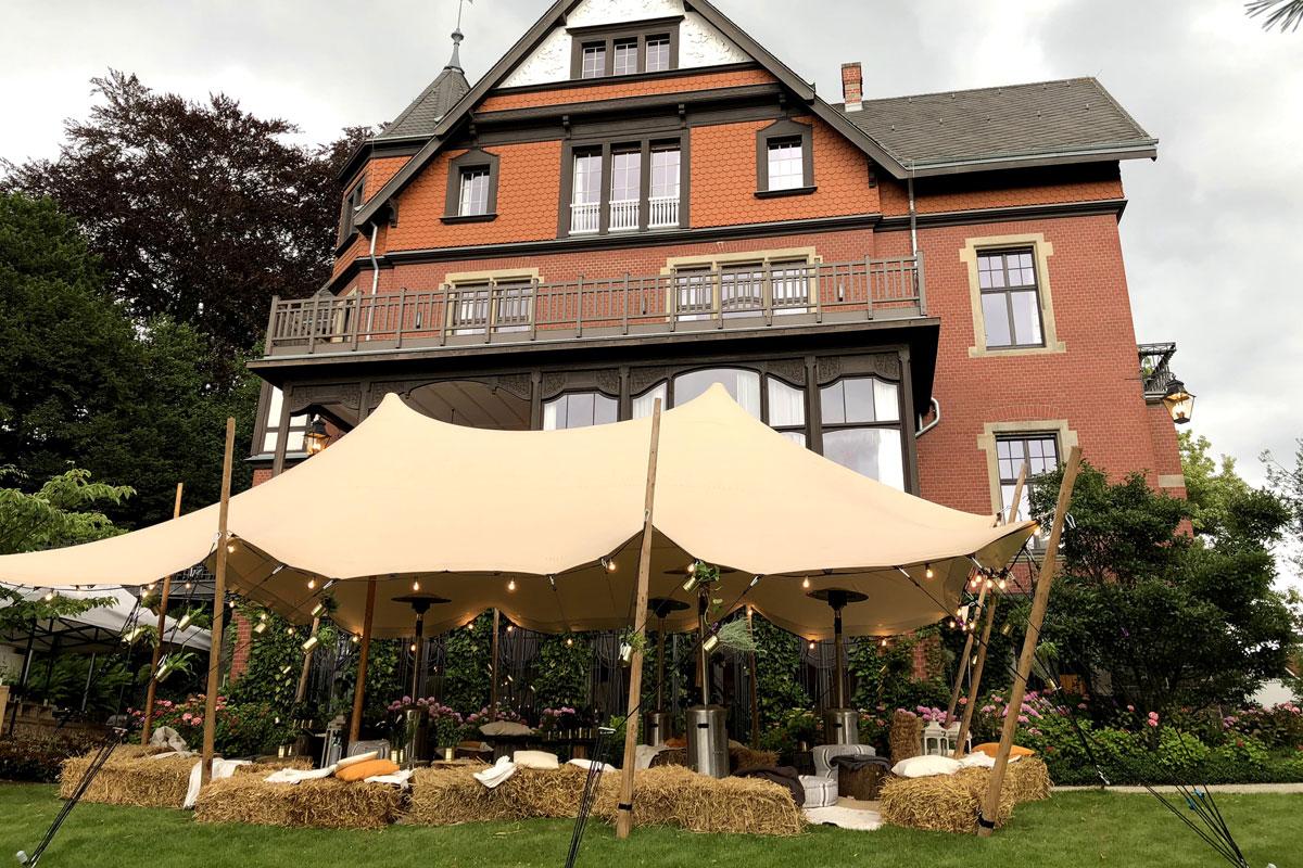 Outdoorlounge mit einem großen Zeltdach vor einer alten Villa