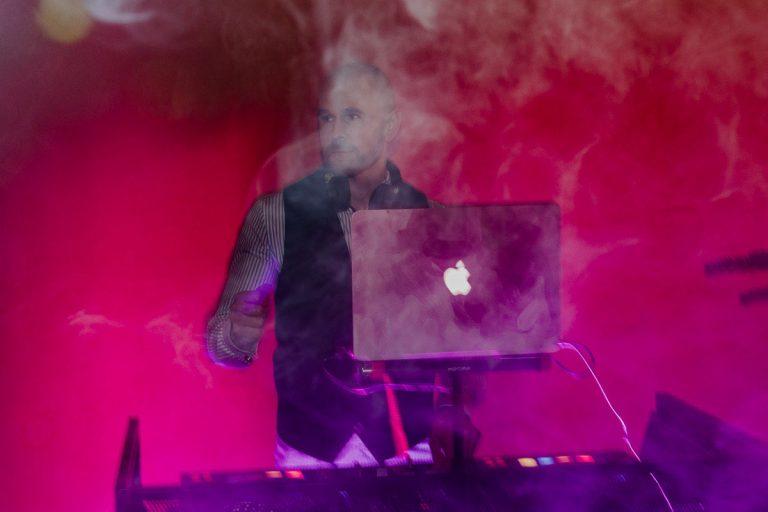 DJ Jerome im Rauch und mit pinker Beleuchtung