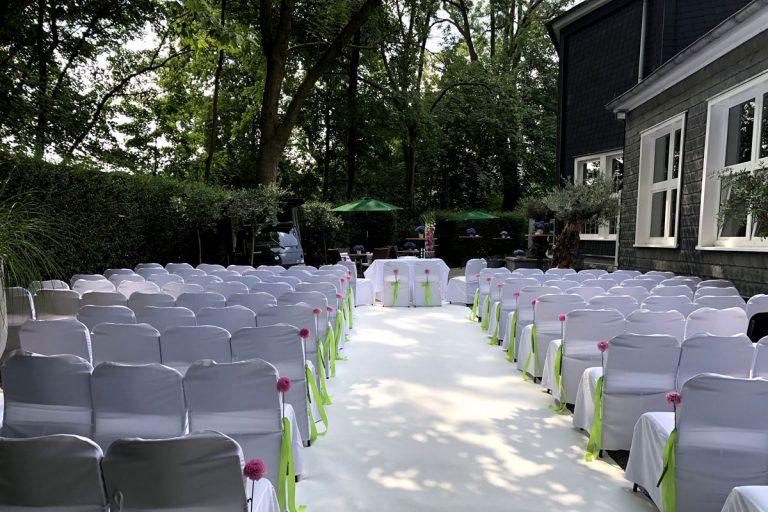 Trauungsbestuhlung mit pinken Blumen und apfelgrünen Bändern für ca. 100 Personen