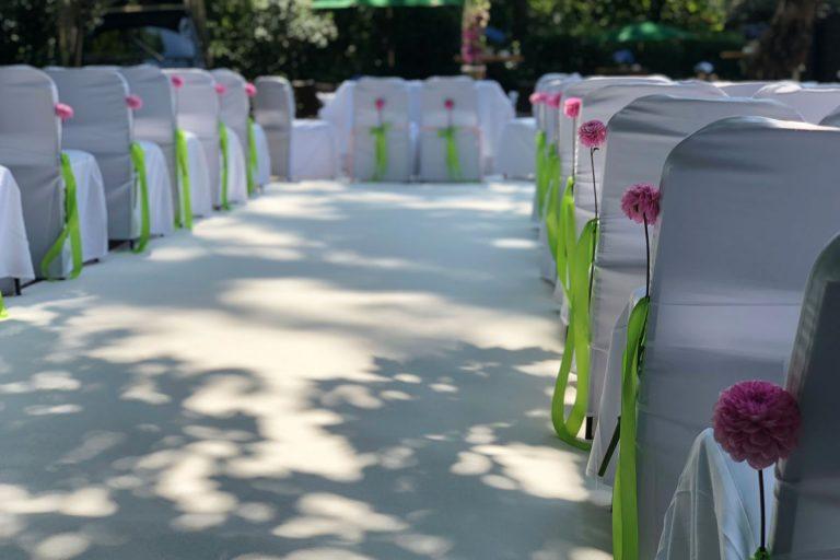 Dekoration der Trauungsbestuhlung mit pinken Blumen und apfelgrünen Bändern