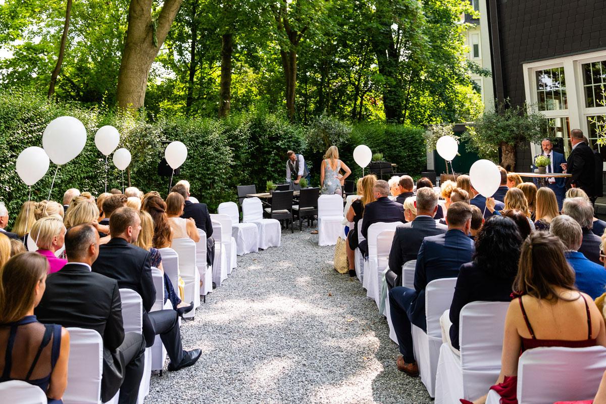 Bestuhlte Trauung im Garten mit weißen Luftballons