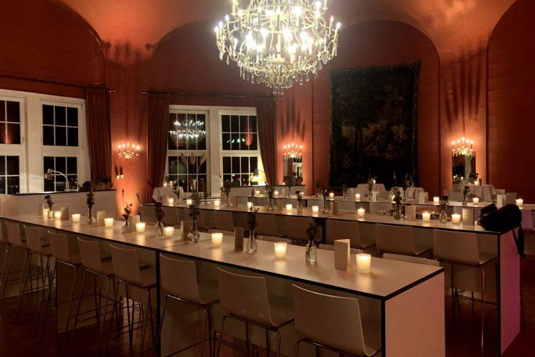 Der große Saal mit eleganten Hochtischen und stimmungsvoller Beleuchtung
