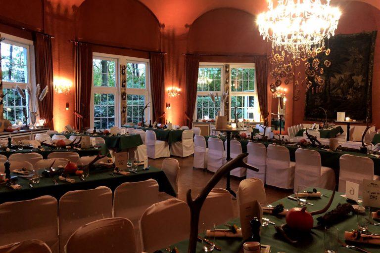 Otoberfestdekoration mit Geweihen auf grünnen Tischen im großen Saal