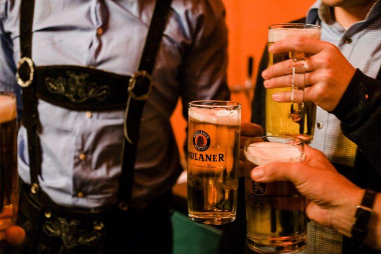 Anstossen mit Biergläsern beim Oktoberfest in Trachten