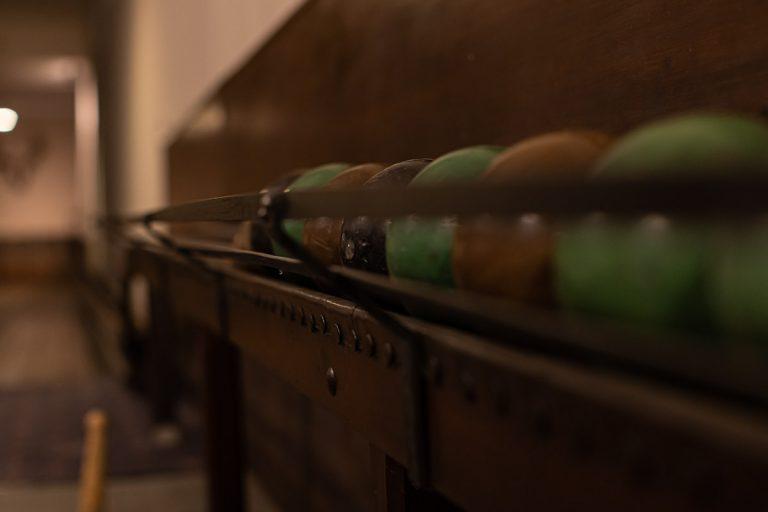 Farbige Kegelkugeln in der Aufbewahrungshalterung der historischen Kegelbahn